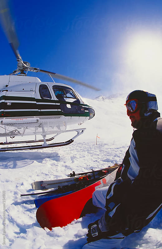 Snowboarder sitting in the snow as helicopter land in the mountains of Alaska by Soren Egeberg for Stocksy United