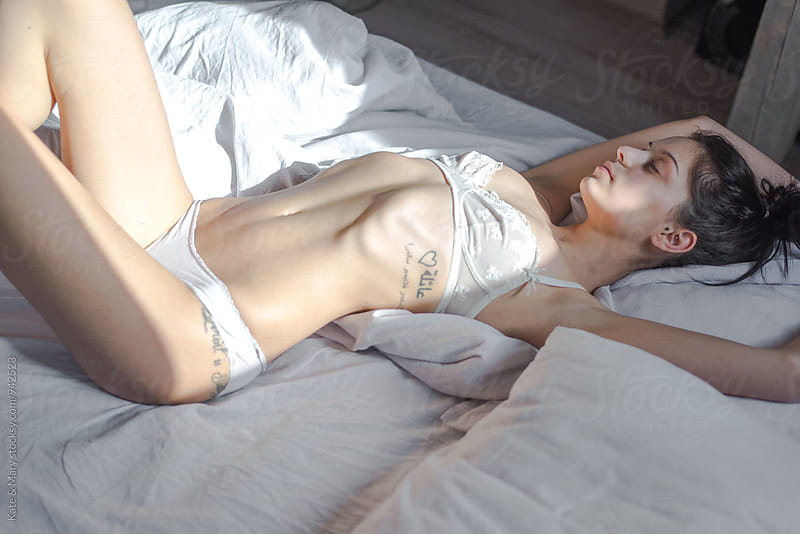 Portrait of sensual woman lay in bed by Kate & Mary for Stocksy United