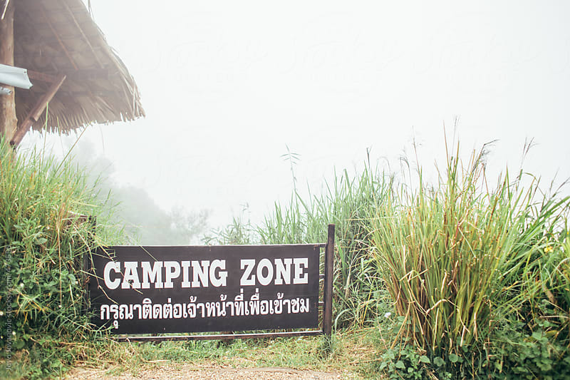 Sign for camping zone with fog in the back ground by Jovo Jovanovic for Stocksy United