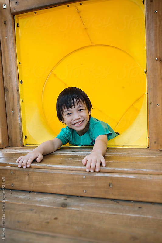 A young kid is all smiles because he is about to go down the slide tunnel by Lawrence del Mundo for Stocksy United