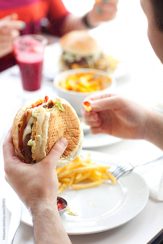 Close up of a male hands holding hamburger.  by Mosuno for Stocksy United