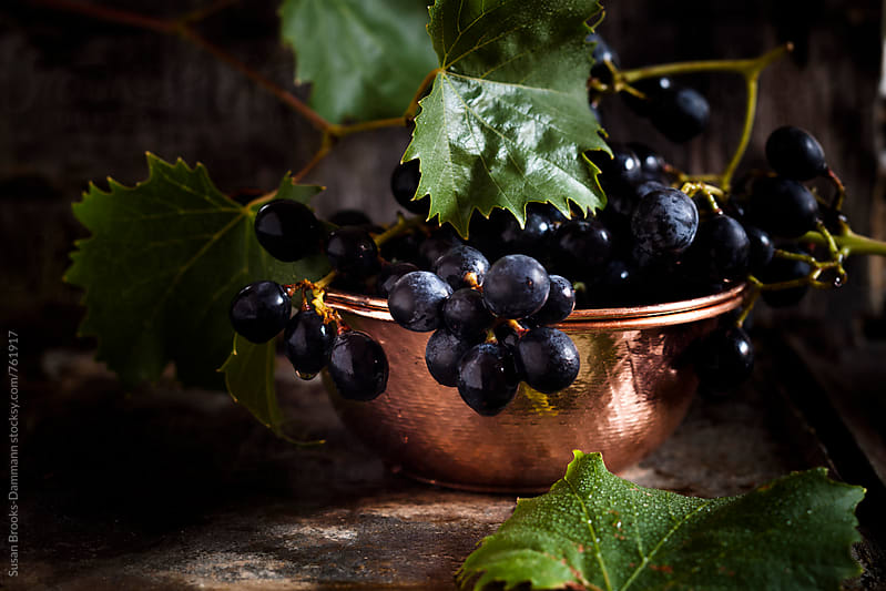 Purple grapes in copper bowl by Susan Brooks-Dammann for Stocksy United