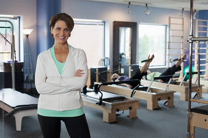 Business owner in her Pilates fitness studio open for business by Edward Bock for Stocksy United