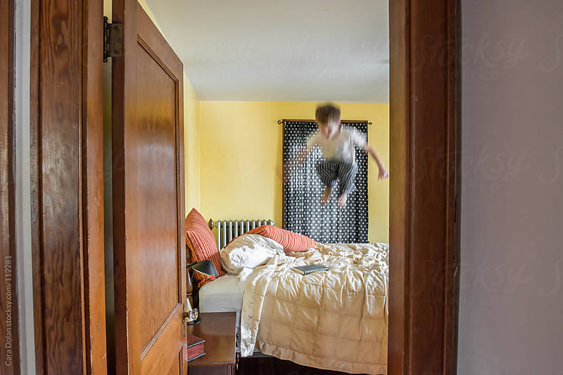 Looking in through a child's bedroom door, you can see him jumping on the bed by Cara Dolan for Stocksy United