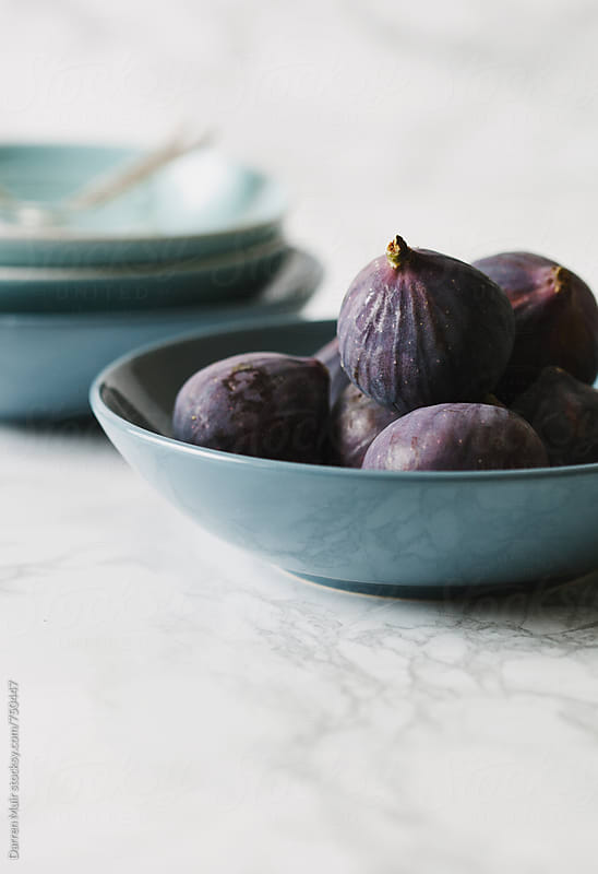 Ripe seasonal figs in a blue bowl. by Darren Muir for Stocksy United