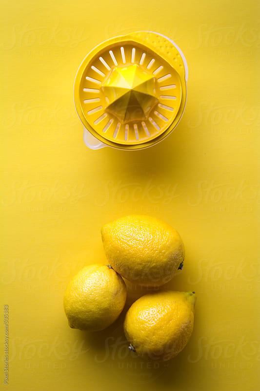 Lemons and juice extractor on yellow background by Pixel Stories for Stocksy United