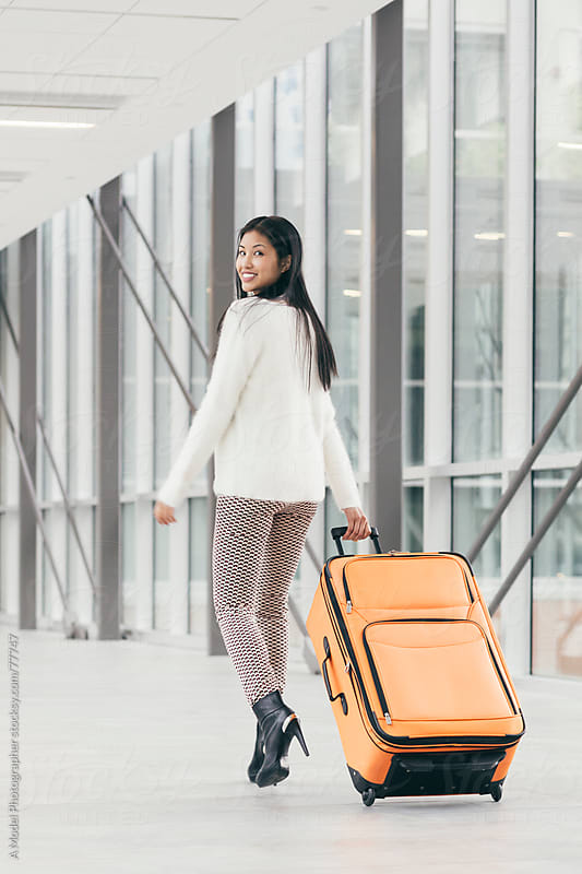 Girl walking away with a suitcase by Ania Boniecka for Stocksy United