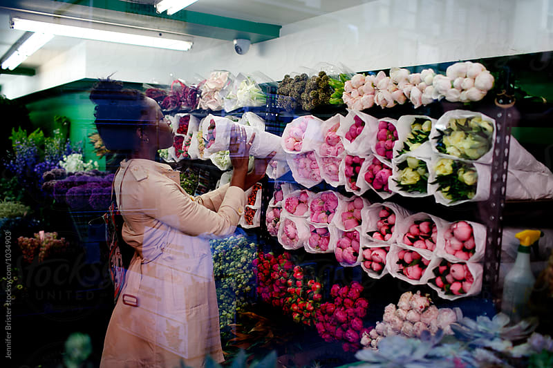 Woman shopping for flowers in flower shop by Jen Brister for Stocksy United