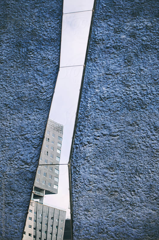 Office building reflected on a vertical window.  by BONNINSTUDIO for Stocksy United