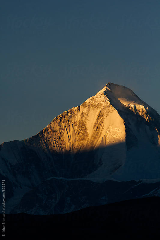 Close up of Mount Dhaulagiri lit up with the warmth of the morning sun. by Shikhar Bhattarai for Stocksy United