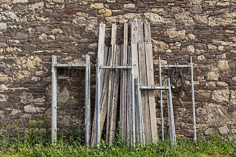 Scaffolding parts leaning against a stone wall by Melanie Kintz for Stocksy United
