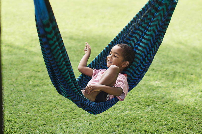 Boy enjoying vacation in a hammock by Per Swantesson for Stocksy United