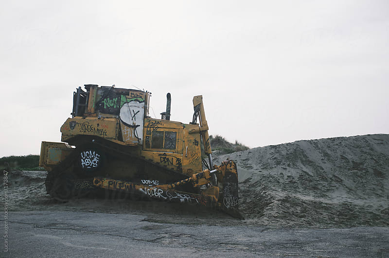 Bulldozer covered in graffiti sitting on sand dunes. by Lucas Saugen for Stocksy United