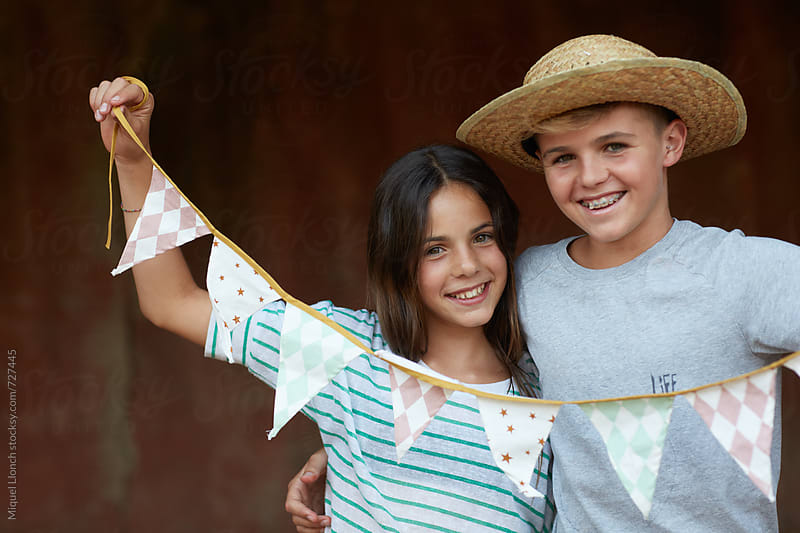 Young girl and and young man celebrating an event by Miquel Llonch for Stocksy United