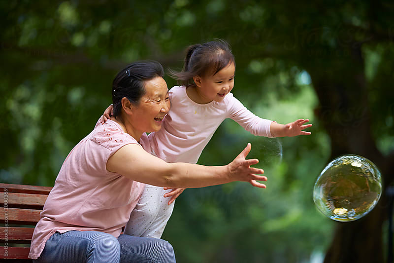happy little asian girl  having fun with her grandmother by cuiyan Liu for Stocksy United