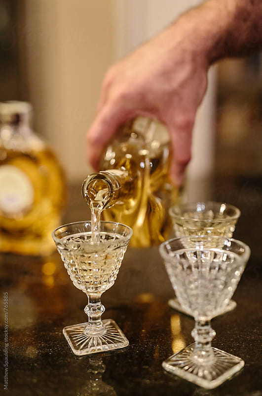 Pouring traditional brandy drink rakia for toast by Matthew Spaulding for Stocksy United
