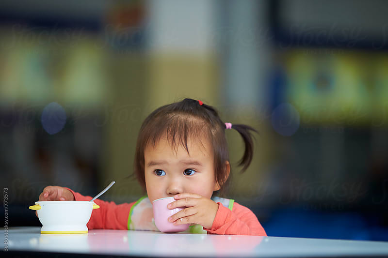 little asian girl having meal indoor by Bo Bo for Stocksy United