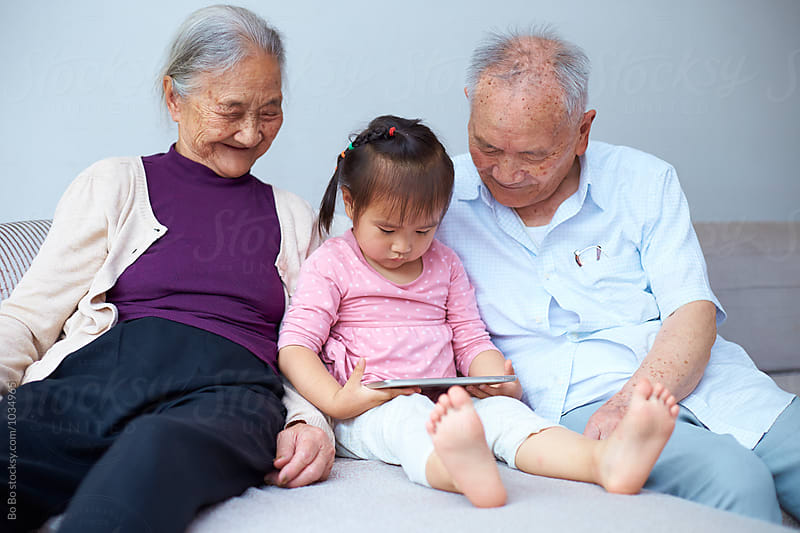 asian senior couple watch their great granddaughter using tablet by Bo Bo for Stocksy United