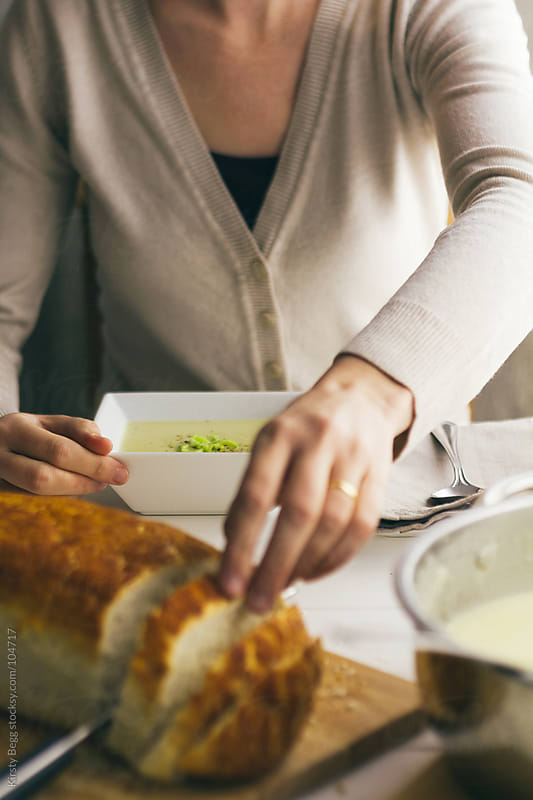 Woman reaching for bread with soup bowl set in front of her by Kirsty Begg for Stocksy United