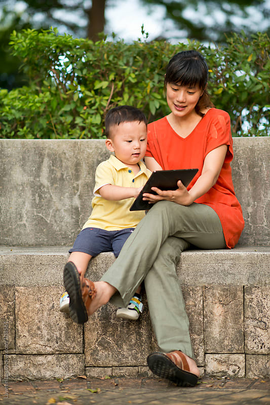 Mother and child look at digital tablet in park by Lawren Lu for Stocksy United