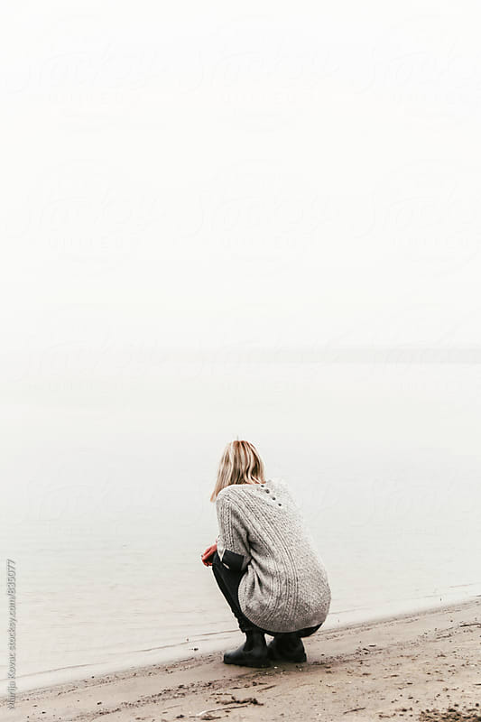 Woman from behind looking at the river - vertical by Marija Kovac for Stocksy United