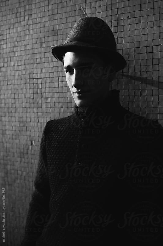 Beautiful young man leaning against the wall by michela ravasio for Stocksy United