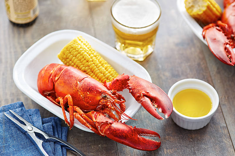 Boiled lobster and corn cob served with butter by Martí Sans for Stocksy United