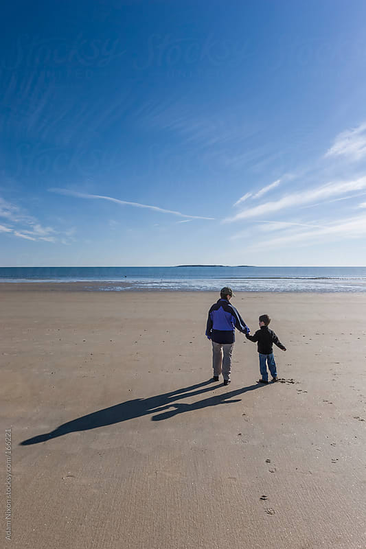 Mother and Child Walking on the Beach by Adam Nixon for Stocksy United