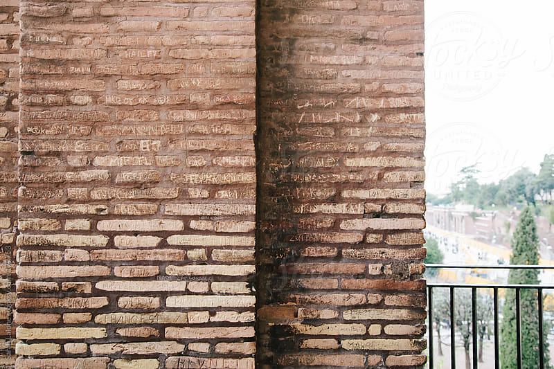 layers of brick graffiti writing on the bricks of the colosseum by Sarah Lalone for Stocksy United