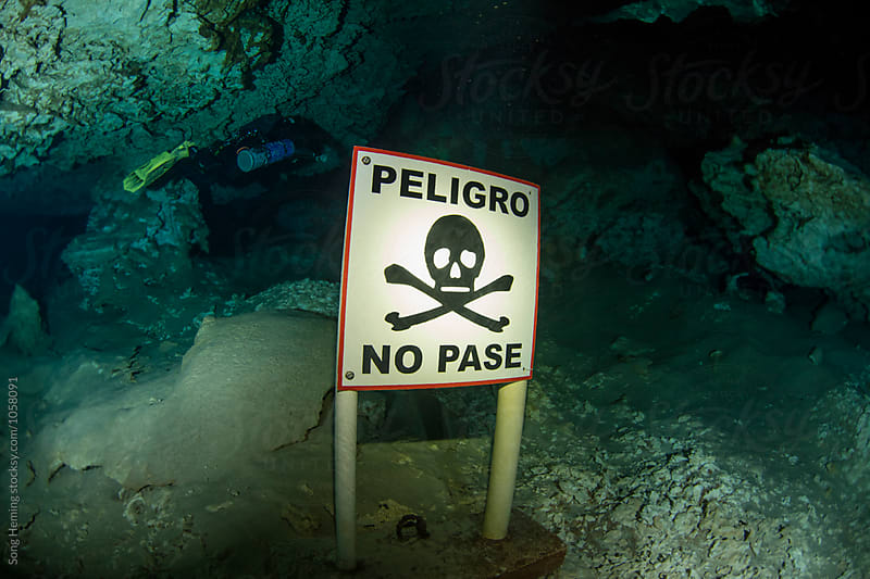A scuba diver with  skeleton warning board in Mexico's  Cenote Tajma ha by Song Heming for Stocksy United