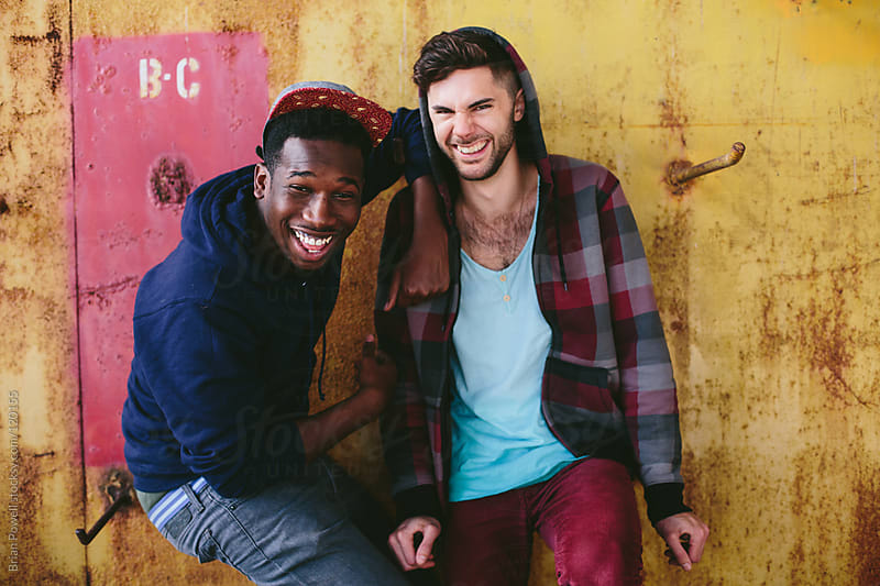 two urban friends laughing hanging out by Brian Powell for Stocksy United