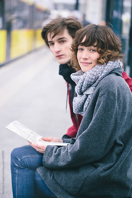 Young couple waiting for a bus by michela ravasio for Stocksy United
