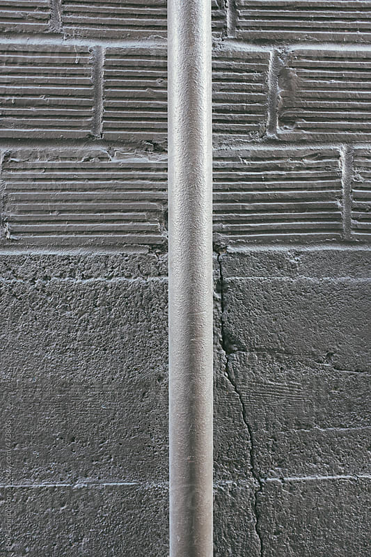 Metal pipe and building wall exterior by Paul Edmondson for Stocksy United