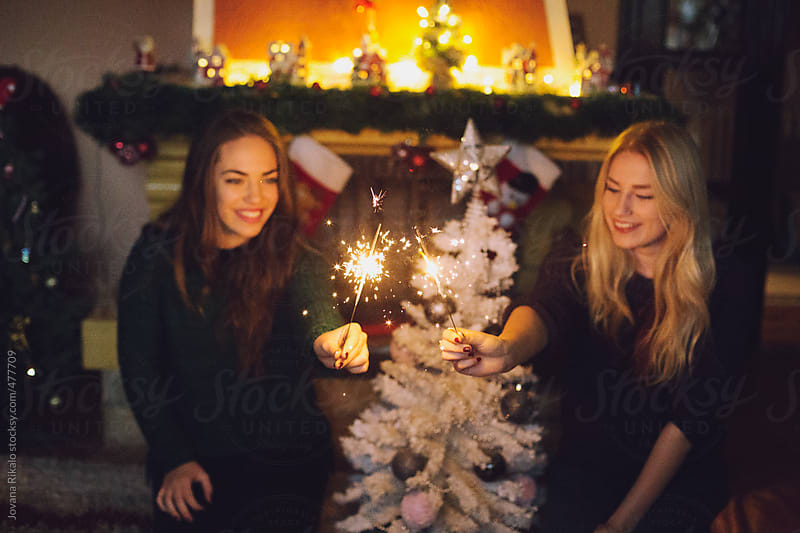 Two female friends smiling and holding sparklers by Jovana Rikalo for Stocksy United
