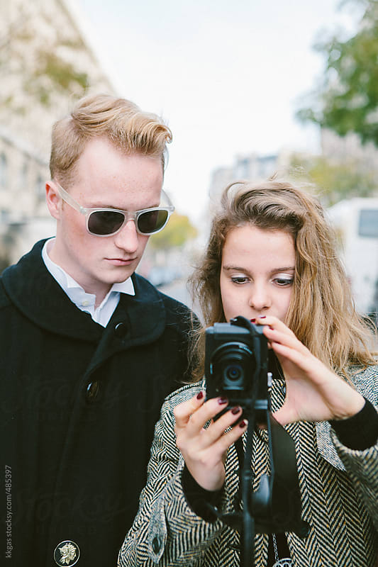 Young couple taking a photo with a compact camera by kkgas for Stocksy United
