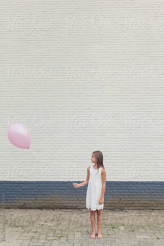 Little girl in front of a white brick wall looking at her pink balloon by Cindy Prins for Stocksy United
