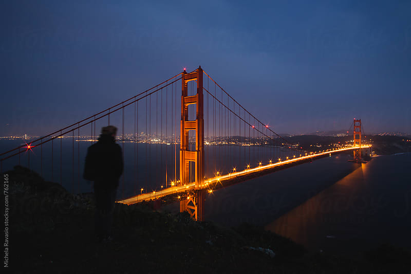 Person viewing the golden gate brige at night by michela ravasio for Stocksy United
