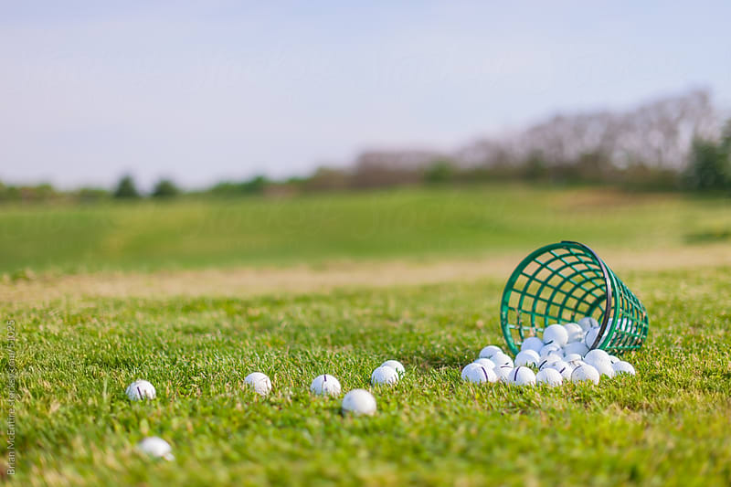 Spilled Bucket of Golf Balls on Empty Driving Range by Brian McEntire for Stocksy United