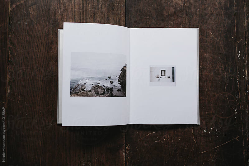 open book with photos of coast by Nicole Mason for Stocksy United