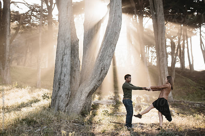 couple dancing together in sunlight through trees by Nicole Mason for Stocksy United