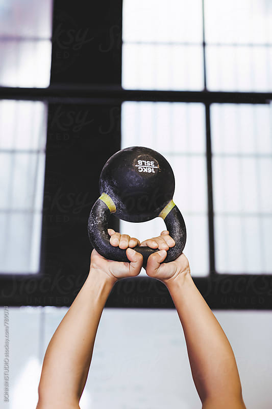 Hands of a woman holding a kettle bell in a gym. by BONNINSTUDIO for Stocksy United