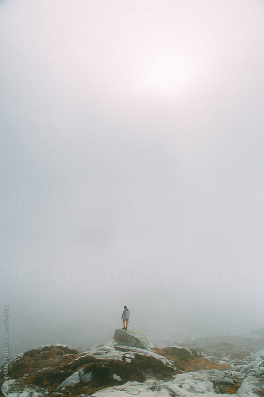 Man Standing Alone On Granite Boulder In Thick Fog by Luke Mattson for Stocksy United