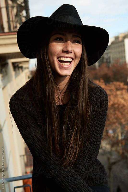 Young woman in black hat laughing on balcony by Guille Faingold for Stocksy United