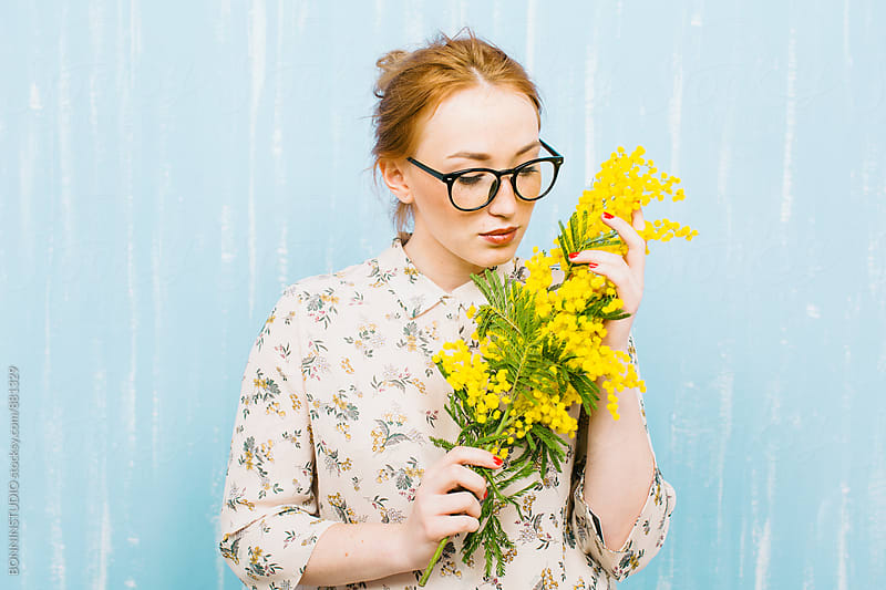 Young ginger woman smelling a bouquet of yellow flowers. by BONNINSTUDIO for Stocksy United
