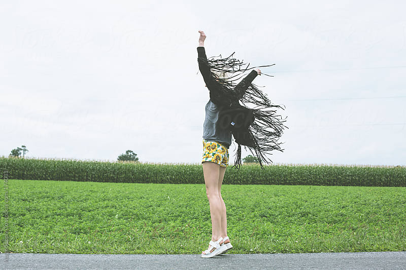 girl dancing with her arms in the air roadside by Image Supply Co for Stocksy United