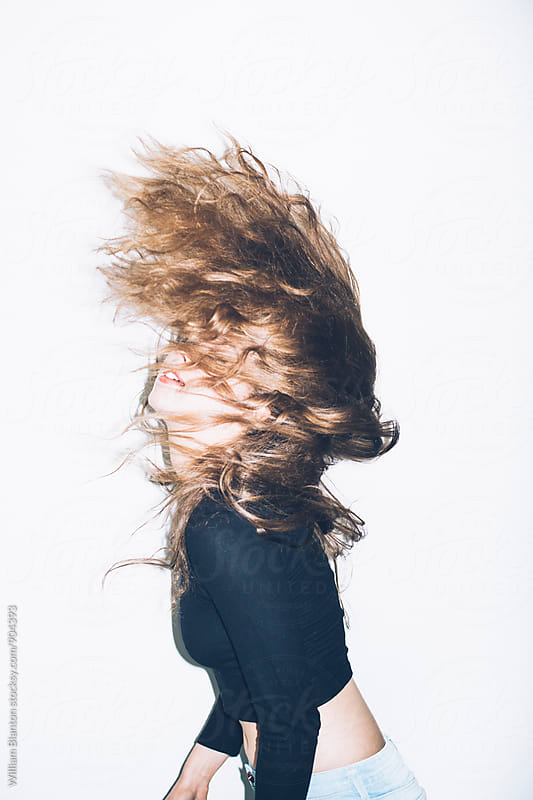 Woman Fashion Model Flinging Hair Against White Background by William Blanton for Stocksy United