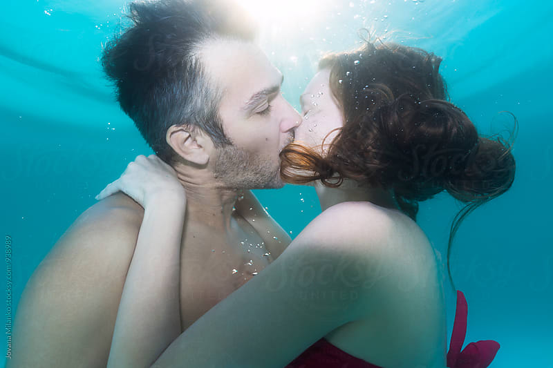 Man and a woman kissing underwater in the swimming pool  by Jovana Milanko for Stocksy United