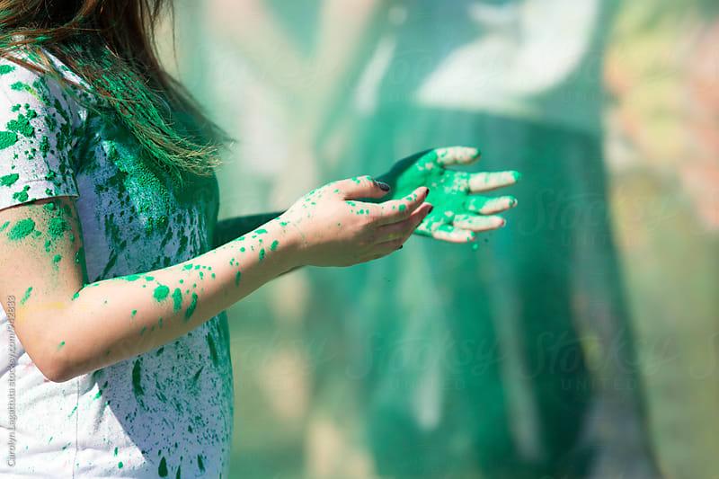 Female at a Holi Festival covered in green powder by Carolyn Lagattuta for Stocksy United