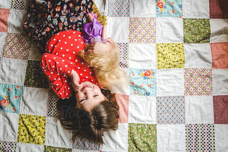Young child lying on a colorful quilt with a doll by Lindsay Crandall for Stocksy United