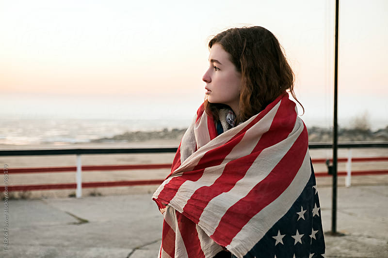Half face of brunette in American flag looking away by Danil Nevsky for Stocksy United